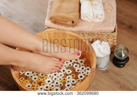 Woman Putting Feet In Basin With Flower Infused Warm Water To Soak It Before Doing Pedicure At Home