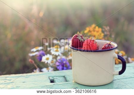 Ripe Strawberries In A Mug On A Background Of Wildflowers. Healthy Summer Breakfast