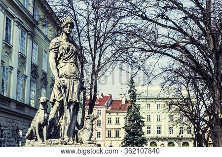 Monument To Diana With A Dog In The Center Of Lviv Square. An Old European City Photo.