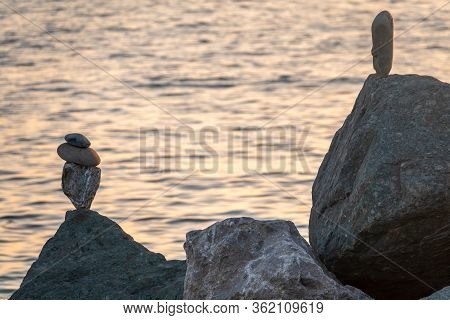 Balancing Stones In Equilibrium. Meditation And Relaxation On The Beach At Sunset.