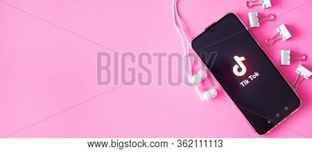Tver, Russia-april 9, 2020, The Tik Tok Logo On The Smartphone Screen On Pink Background With Headph