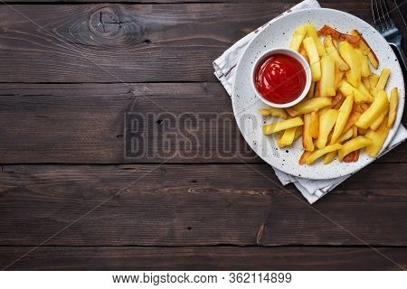 Fried French Fries Potatoes With Tomato Ketchup Sauce On A Plate. Wooden Background. Copy Space.