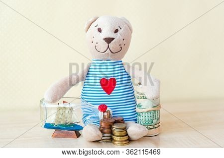 Toy Teddy Bear Is Dreaming. Saving Money For Dreams And Future Concept. Dream Of A Yacht, Travel, Va