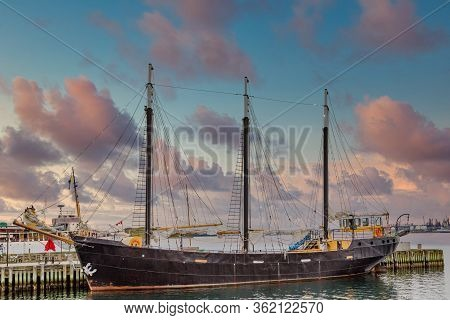 A Black Three-masted Ship In A Harbor In Halifax, Nova Scotia