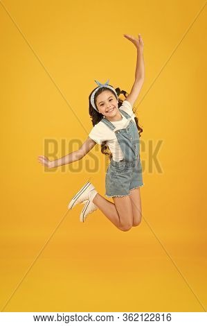 Small Girl Jump Yellow Background. Enjoy Freedom. Childrens Day Concept. Spirit Of Freedom. Active G