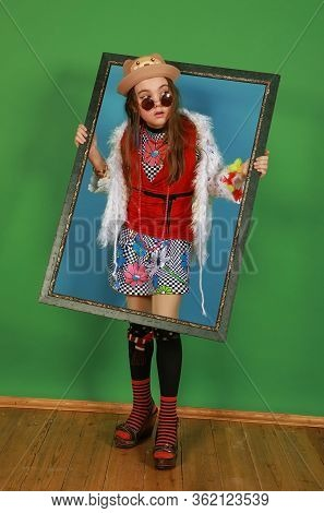Little Girl Freak Holds A Picture Frame In A Studio On A Green Background