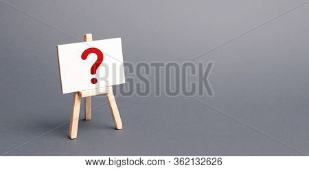 Easel With A Question Mark. Curiosity, Mystery, Investigation Research. Poll Survey. Announcement Of