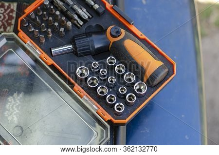 Screwdriver With A Set Of Bits. Used Bit Set For Screwdriver In Plastic Box. Hand Tools In The House