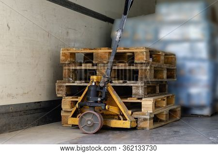 Hand Pallet Truck Inside The Truck. Empty Wooden Pallets And Pallets And Goods In The Background. Un