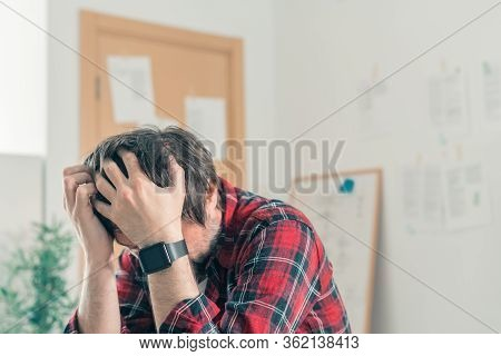 Disappointed Freelancer At Home Office With His Head In Hands, Selective Focus