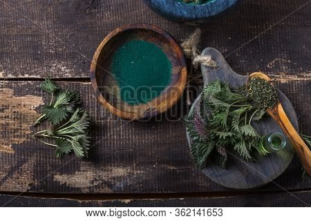 Fresh Stinging Nettle Leaves On Wooden Table.urtica Dioica Oil With Spirulina Powder, A Healthy Supp