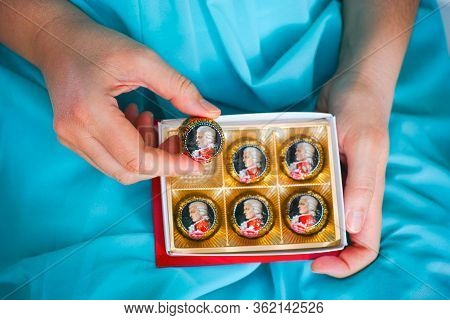 Tambov, Russian Federation - February 14, 2020 Woman Taking Mozart Candy From Open Candy Box.