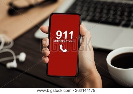Emergency Call Concept. Top View Of Hands Holding Smart Phone With Number 911 On Red Screen Over Off
