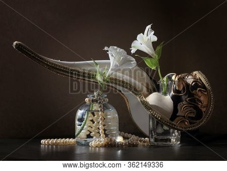 Retro Style Still Life With Beaked Venetian Carnival Plague Doctor Mask, Two Alstroemeria Flowers In