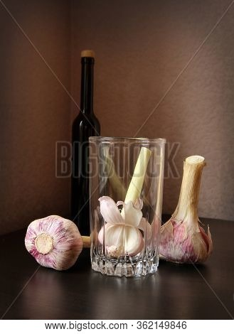 Three Garlic Bulbs, Vintage Glass Beaker And Black Bottle With Olive Oil Against A Low Key Backgroun