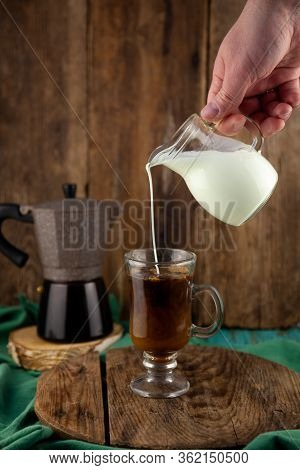Milk Is Poured Into Decanter Coffee. Geyser Coffee Maker, Creamer On A Wooden Table. Glass Cup With