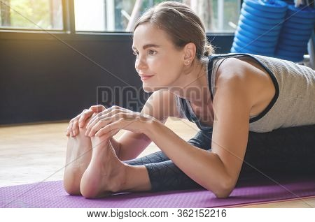 Young Woman Practicing Yoga, Sitting On Exercise Mat Bending Forward And Holding Legs. Woman Practic