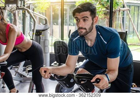 Portrait Of Young Man Exercising Using Stationery Bike In Gym With A Group Of People. Fitness Class