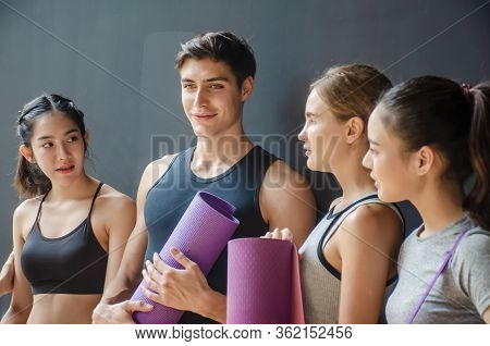 Group Of Young Sporty People With Fitness Yoga Exercise Mats Standing Beside Black Wall.students Tak