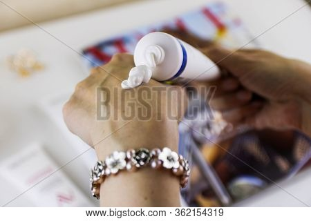 Close Up Of A Woman Putting Nourishing Cream Oh Her Hands.