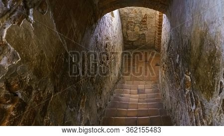 Staircase In An Old Castle Going To The Dungeon. Medieval And Gothic Concept. Background Of Text.