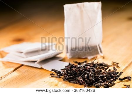 Tea bag on wooden background. Tea bag and tea leaves on a wooden background.