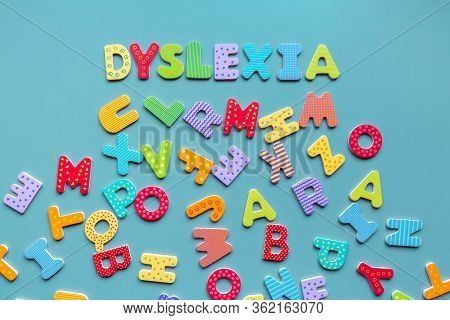 Dyslexia Word Written Of Wooden Letters And Scattered Letters Below. Inscription Dyslexia Formed Wit