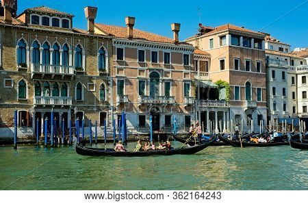 Venice, Italy - June 2, 2019: Three Gondolas Ferry Tourists Along The Grand Canal Past Ornate Old Bu