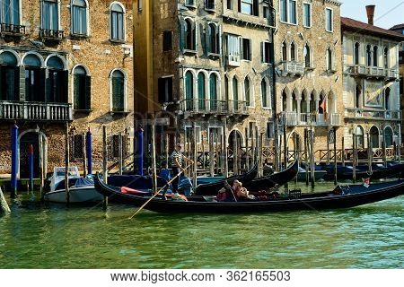 Venice, Italy - June 2, 2019: A Gondolier Takes A Couple Of Tourists For An Excursion On The Grand C