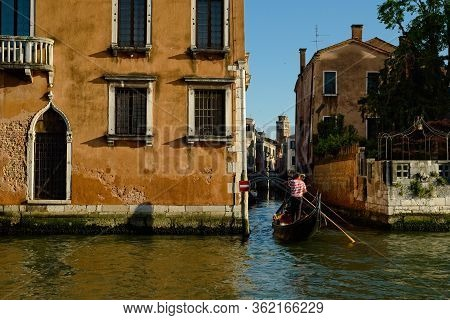 Venice, Italy - June 2, 2019: Two Gondoliers On The Grand Canal Enter A Narrow Canal To The Side Clo