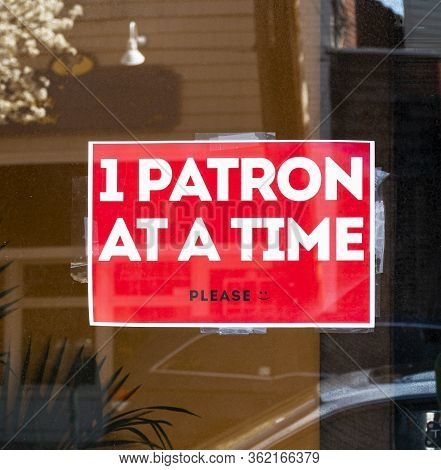 Restaurant Has Sign In Window Reading 1 Patron At A Time Please To Pick Up Take Out Only Food During