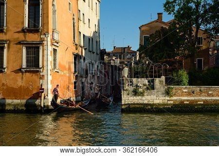 Venice, Italy - June 2, 2019: Two Gondoliers On The Grand Canal Enter A Narrow Side Canal Between Ol