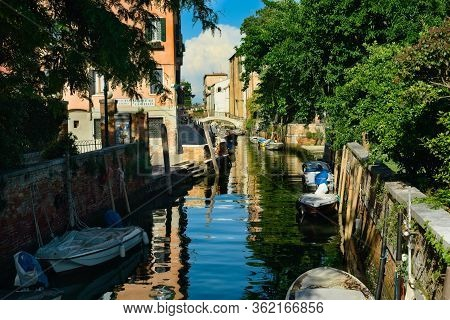 Venice, Italy - June 2, 2019: Boats Line A Quiet Canal In Venice. To The Right (foreground) Lies The