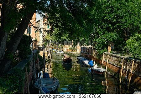 Venice, Italy - June 2, 2019: Two Small Boats Make Their Way Down A Quiet Canal In Venice, With Many