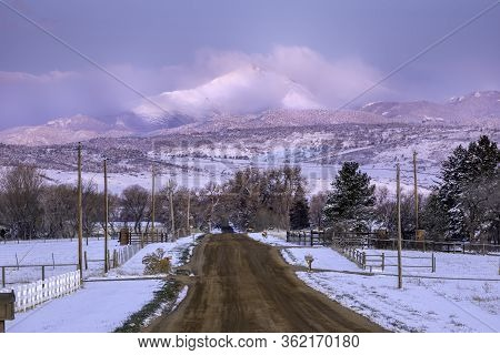 A Dirt Urban Road Leading To A Snow Capped Longs Peak Mountain After A Fresh Snow Fall
