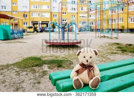 Forgotten Toy Teddy Bear Sitting On The Bench In The Empty Quarantined Playground On Sunny Spring Da