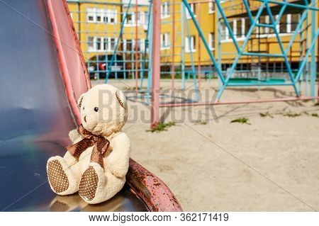 Forgotten Toy Teddy Bear In The Empty Quarantined Playground On Sunny Spring Day