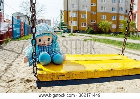 Forgotten Toy Teddy Bear Sitting On Yellow Swing In The Empty Quarantined Playground On Sunny Spring