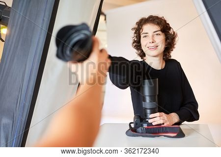 Young photographer chooses a camera lens for the photo shoot in the studio