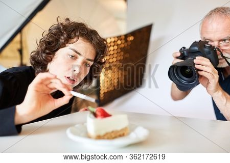 Food stylist and photographer with camera taking photos of food