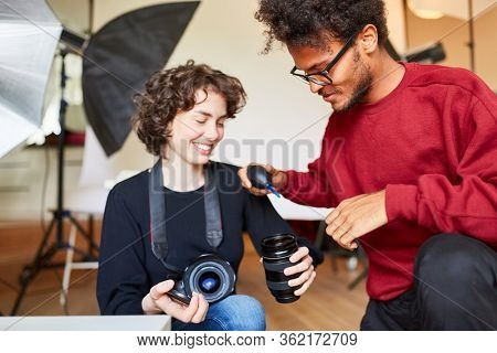 Photographer and photo assistant together clean a camera lens