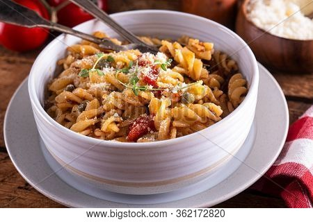 A Bowl Of Delicious Pasta Puttanesca With Rotini, Anchovies, Black Olives, Tomatoes And Capers.