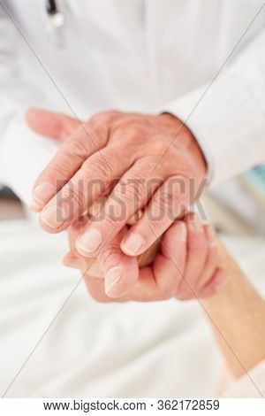 Doctor or nurse consoles senior patient and holds her hands thoughtfully