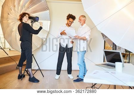 Photographer with art director and photo assistant in the photo studio preparing a photo shoot
