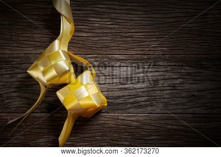 directly above of ribbon ketupat on the wooden background