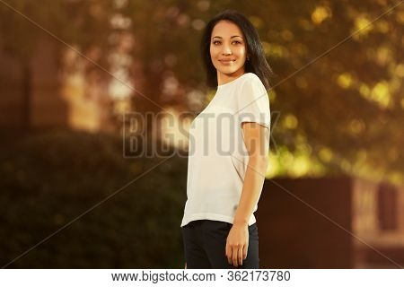 Happy young beautiful woman walking on city street Stylish fashion model in white t-shirt with bob hairstyle