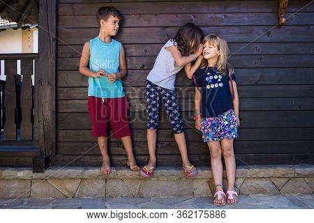 Kids Gossiping. Girl Whispering Something To Other Girl, Boy Eavesdropping. Kids Playing, Playfulnes
