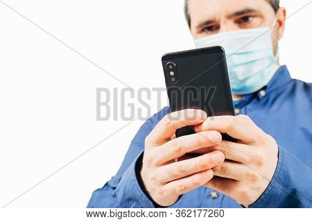 Man In Medical Mask Looking At Smartphone On White Background