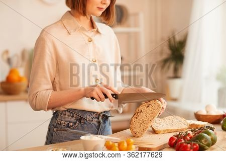 Mid-section Portrait Of Modern Young Woman Cutting Fresh Wholewheat Bread While Making Breakfast In