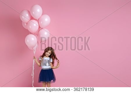 Smiling Adorable Little Child Girl Posing With Pastel Pink Air Balloons Isolated Over Pink Backgroun